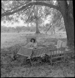 1998.97.571 Jean Buxton sitting at a picnic table in the shade of a large tree at Gogrial, Southern Sudan