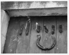 1965.5.1.460 Amulets (horse-shoe and rodent feet) on door of house in Lake District, photographed by Ernest G. Rathenau c. 1950