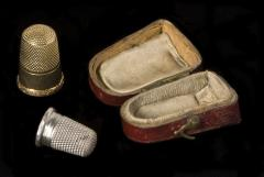 1961.2.038 and 1961.2.039 Thimbles (the silver one is a child's) and box donated by Canziani
